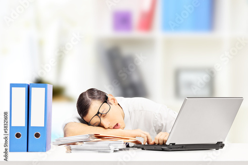 Exhausted businessman sleeping on a desk in his office
