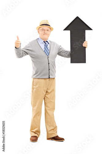 Smiling senior man holding arrow pointing up and giving thumb up
