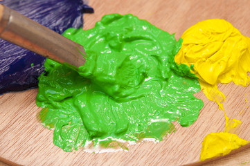 Closeup of green and yellow watercolor paints being mixed with a