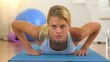 Healthy woman doing push ups and looking at camera