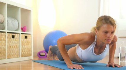 Healthy blonde woman doing push ups