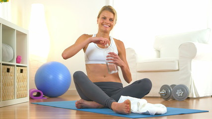 Healthy woman drinking water during workout