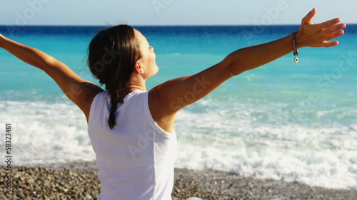 Woman at the beach rising hands to the sky, rear view