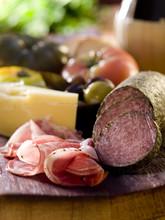 Rustique plateau de bois avec de la viande, du fromage et des légumes.
