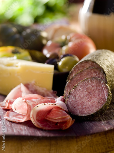 Rustic wood platter with meat, cheese and vegetables.