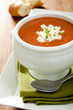 Closeup of tomato soup with crumbled goat cheese.