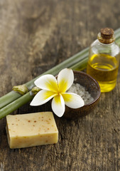 soap, frangipani ,salt in bowl and bamboo grove on old wood