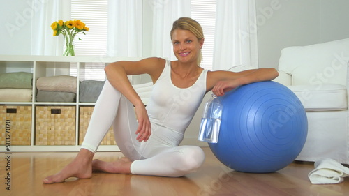 Healthy woman with balance ball drinking water