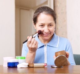 woman putting make up on her face