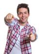 Mann mit karriertem Hemd zeigt mit beiden Fingern zur Kamera