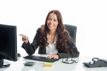 Geschäftsfrau am Schreibtisch zeigt auf den Bildschirm