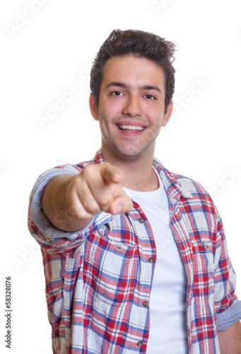 Mann mit kariertem Hemd zeigt mit Finger zur Kamera
