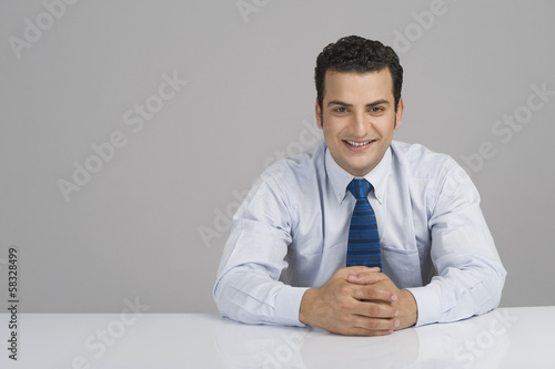 Businessman smiling with hands clasped