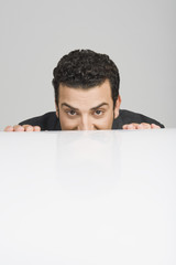 Businessman peeking over a desk