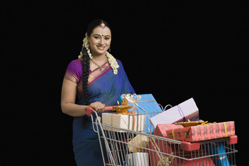 Woman carrying Diwali gifts in a shopping cart