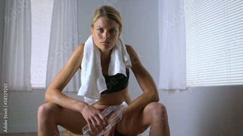 Strong woman wiping sweat off face