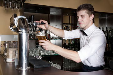 Bartender in white shirt serving beer in front of the bar.