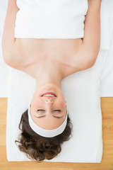 Young brunette lying on massage table with eyes closed