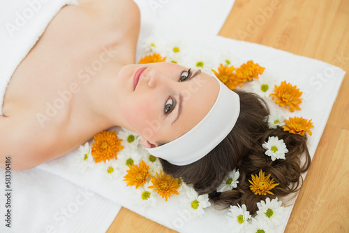 Beautiful woman with flowers in beauty salon