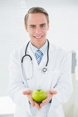 Portrait of a smiling male doctor with a green apple