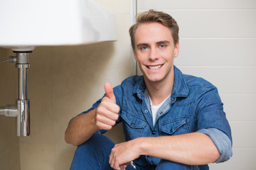 Handsome plumber gesturing thumbs up besides washbasin