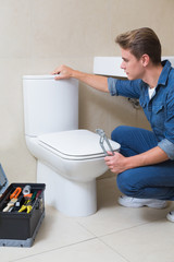 Handsome plumber with toolbox doing toilet reparation