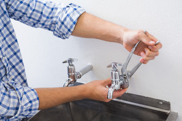 Plumber hand's fixing water tap with pliers