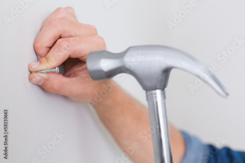 Hands hammering nail in wall