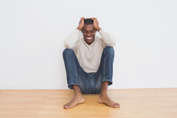 Angry casual Afro man sitting on floor against wall