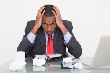 Frustrated Afro businessman with head in hands at  desk