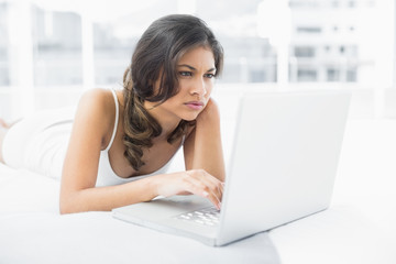 Serious casual woman using laptop in bed