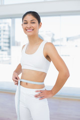 Smiling woman measuring waist in fitness studio