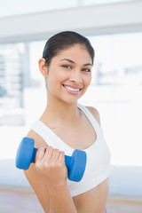 Woman exercising with dumbbell in fitness studio