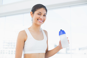 Smiling fit woman with water bottle in fitness studio