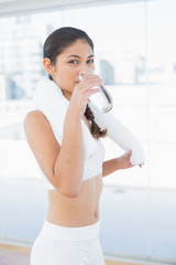 Woman with towel around neck drinking water