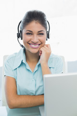 Businesswoman wearing headset in front of laptop