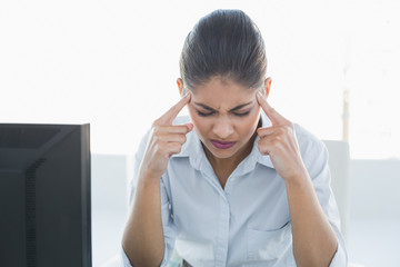 Tired businesswoman suffering from headache in front of computer