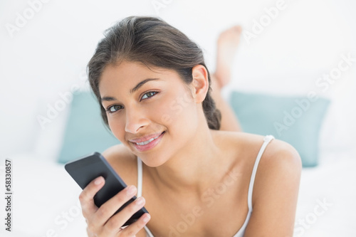 Smiling woman with mobile phone in bed
