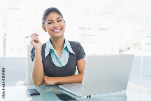 Smiling businesswoman with laptop at office
