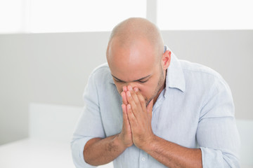 Sad casual man with hands to his face at home