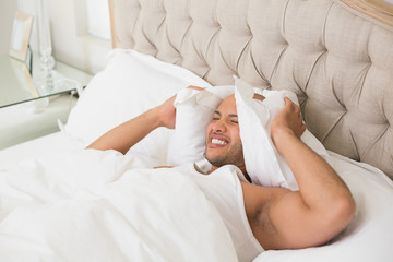 Sleepy man covering ears with pillow in bed