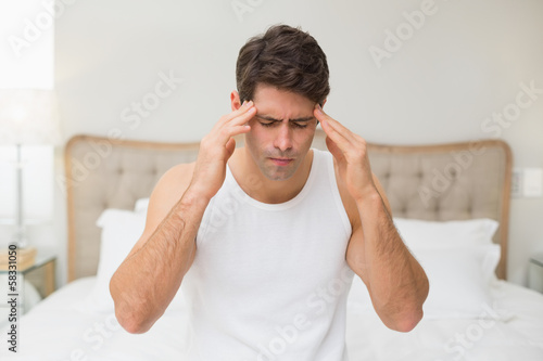 Young man suffering from headache in bed