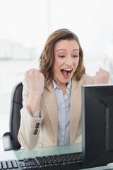 Elegant businesswoman cheering at office desk