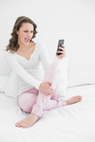 Cheerful woman looking at mobile phone in bed