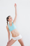 Sporty female stretching hand in fitness studio