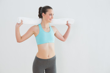 Fit young woman with towel around neck against wall