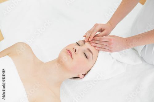 Hands massaging a beautiful woman's forehead