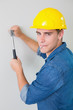 Portrait of handyman hammering nail in wall