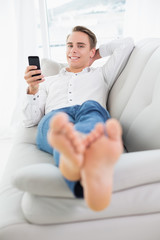 Relaxed young man lying on sofa and text messaging