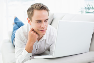 Relaxed casual young man with laptop lying on sofa